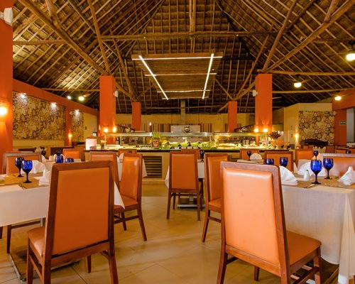 A large restaurant interior with multiple dining tables buffet and high thatched ceiling.