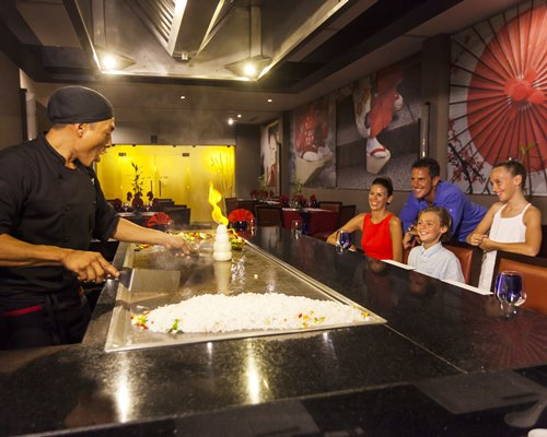 A family in a restaurant watching hibachi chef preparing food.