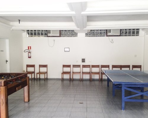 A recreational room with foosball and table tennis.