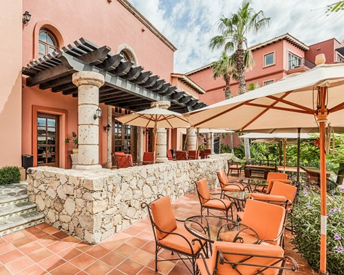 An outdoor dining area with patio and umbrellas alongside the resort.