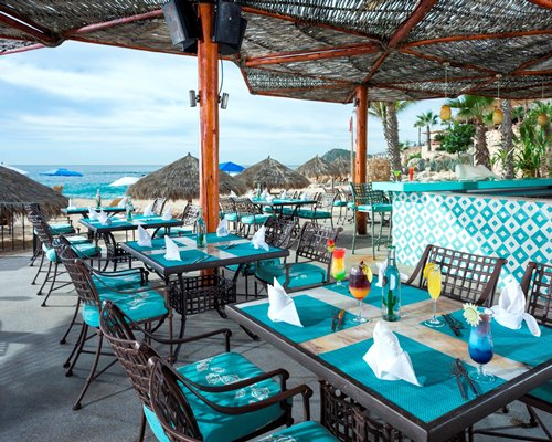 An outdoor fine dining area with thatched sunshades alongside the beach.