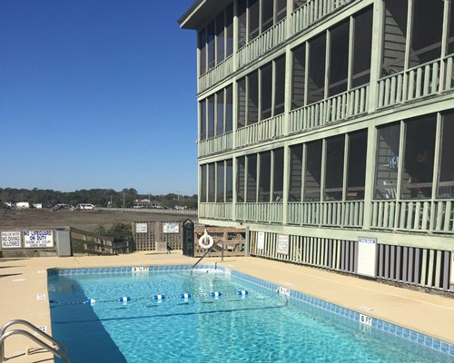 Exterior view of multiple unit balconies with outdoor swimming pool.
