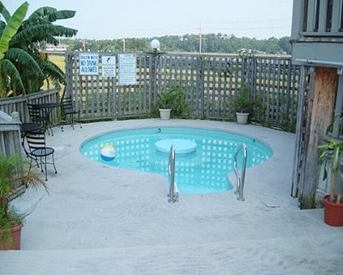 An outdoor swimming pool with patio furniture.