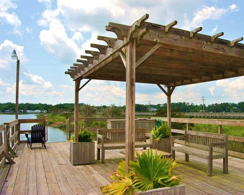 An outdoor recreational area with a wooden deck alongside the waterfront.