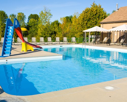 Outdoor swimming pool with a playscape chaise lounge chairs and sunshades surrounded by wooded area.