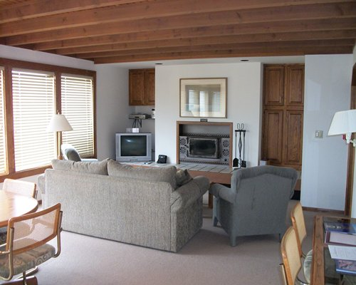 An open plan living room and dining area with television and fireplace.