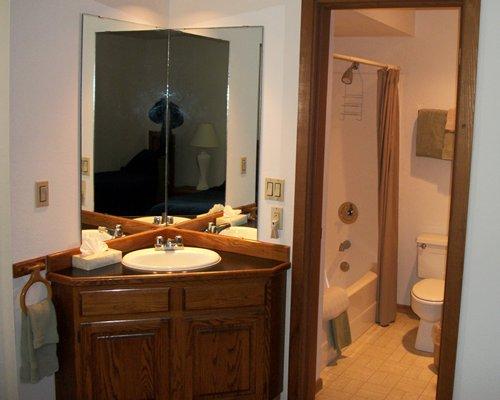 A single sink vanity alongside bathroom with a shower and bathtub.
