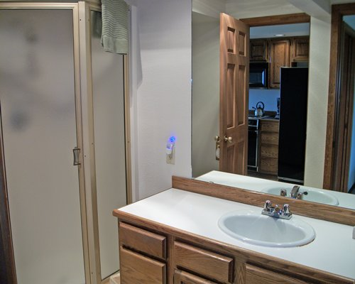 A bathroom with a closed sink vanity and shower stall.