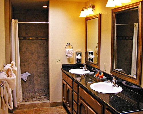 A bathroom with bathtub shower and double sink vanity.