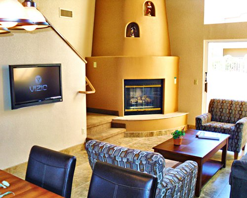 A well furnished living room with a dining area television and fireplace.