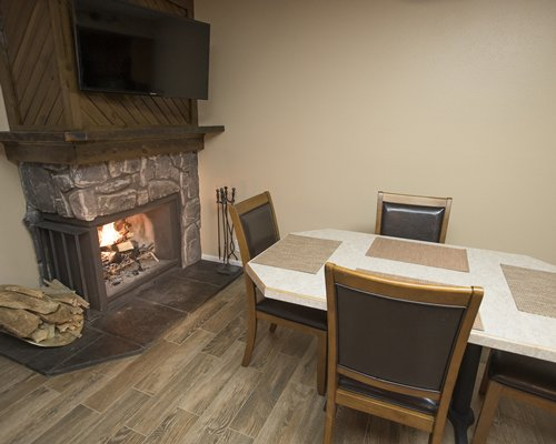 A well furnished dining table with a fireplace and television.