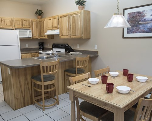 An open plan dining and kitchen area with a breakfast bar.