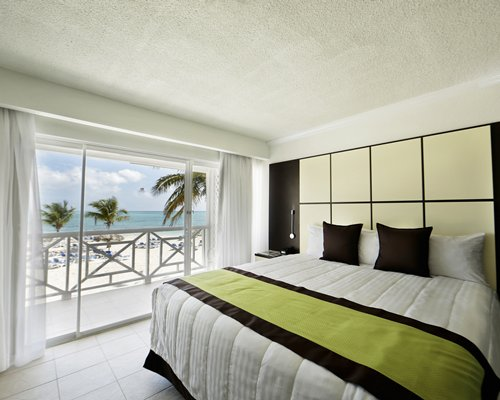 A well furnished bedroom with queen bed balcony and ocean view.