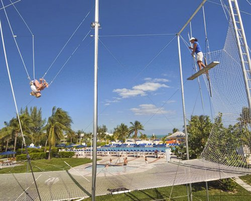 View of two persons performing trapeze alongside the pool.