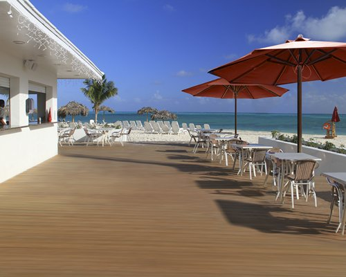 An outdoor dining area with patio and umbrellas alongside the beach.