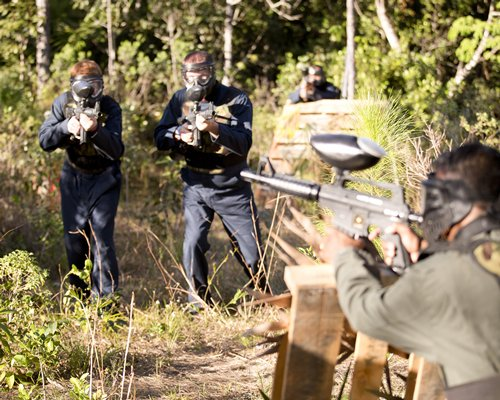 A group of people playing paintball in a wooded area.