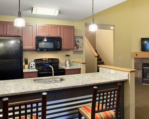 A well equipped kitchen with breakfast bar television and fireplace.
