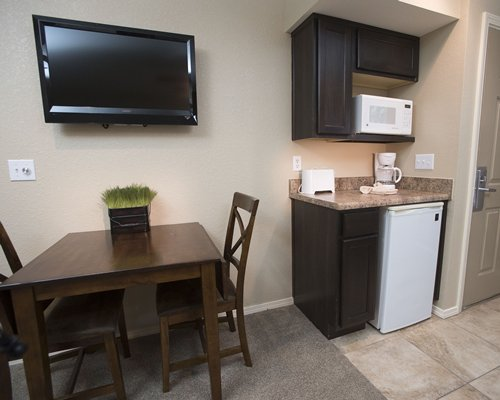 An open plan kitchen with a dining area and television.