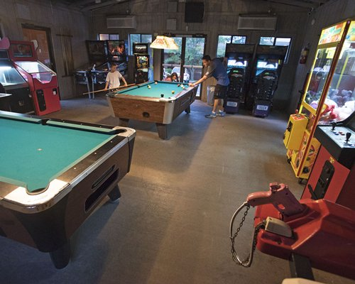An indoor recreation room with pool tables and arcade games.