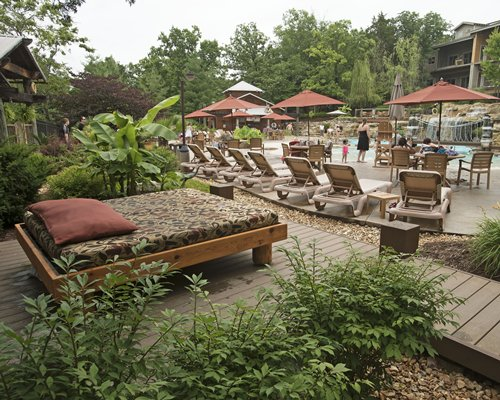 An outdoor swimming pool with chaise lounge chairs alongside landscaping.