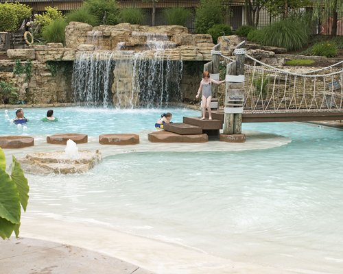 Large swimming pool with a wooden bridge and grotto pool.