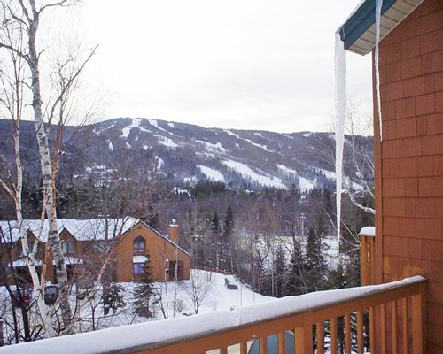 A balcony view of resort condos surrounded by mountains.