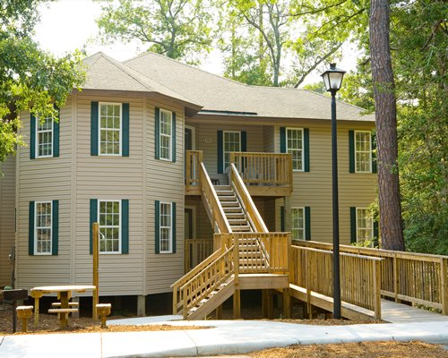 A two story resort condo with a 2nd floor wooden deck surrounded by trees.