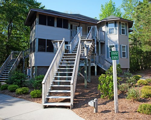 An exterior view of a resort condo with stairway and landscaping.