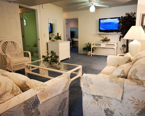 A well furnished living room with pull out sofa and a television.