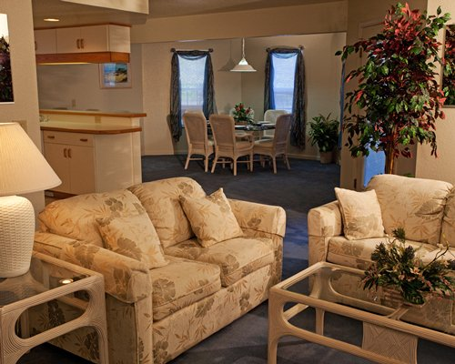 A well furnished living room dining and kitchen area.
