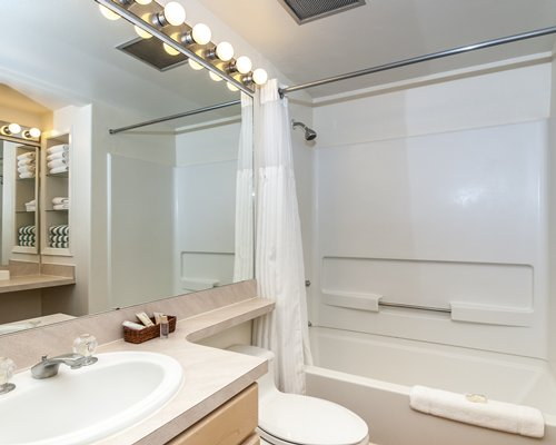 A bathroom with bathtub shower and a single sink vanity.