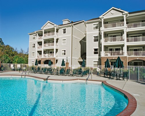 View of multiple unit balconies with an outdoor swimming pool chaise lounge chairs and sunshades.