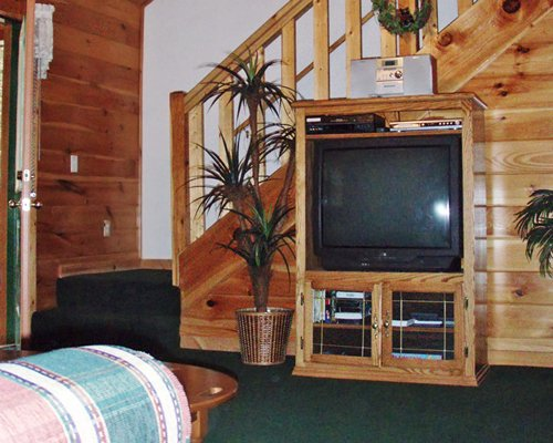 Living room with a television alongside the wooden staircase.