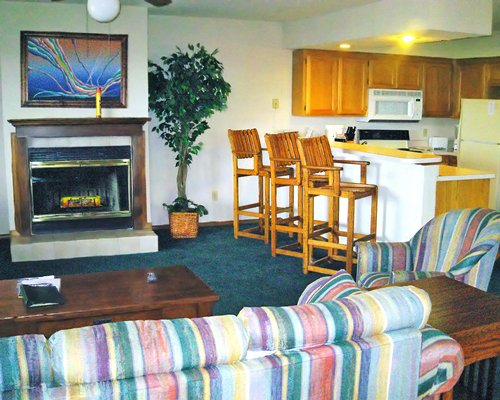 A well furnished living area with a fireplace alongside a kitchen and a breakfast bar.