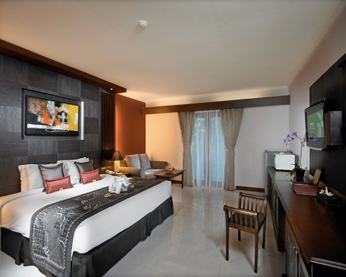 A well furnished bedroom with a king bed television and outside view.