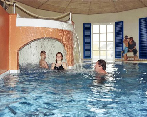 Indoor swimming pool with a grotto pool and outside view.
