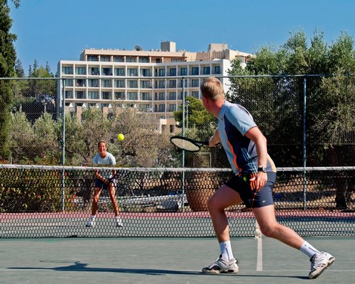Two people playing tennis alongside multi story resort condos.