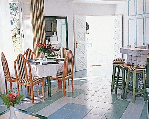 A well furnished dining room with a breakfast bar and an outside view.