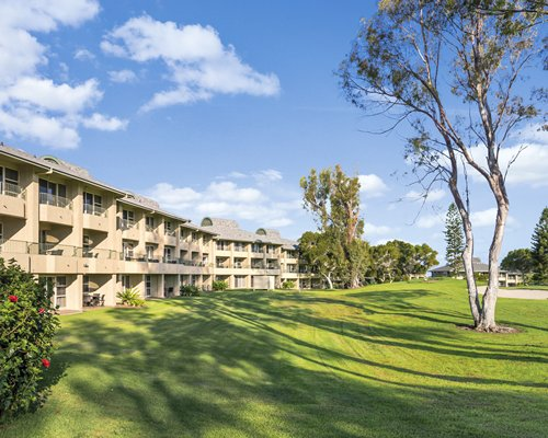 A well maintained lawn alongside the multi story Paniolo Greens resort.