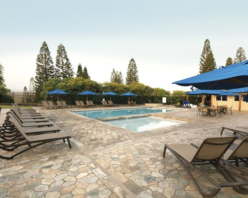 An outdoor swimming pool with chaise lounge chairs patio and sunshades.