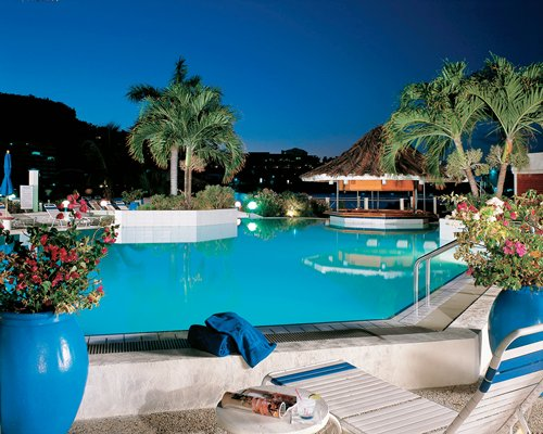 Night view of an outdoor pool with chaise lounge chairs and palm trees alongside a snack bar.