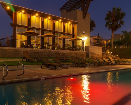 An outdoor swimming pool with chaise lounge chairs and patio furniture at night.