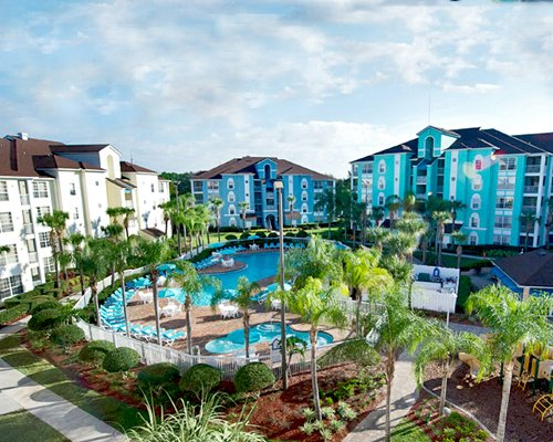 An outdoor swimming pool and chaise lounge chairs alongside multi story resort units.