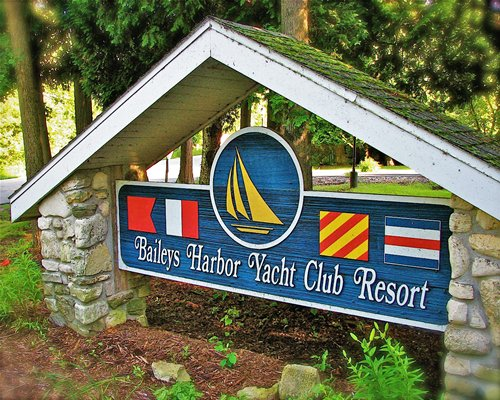 Signboard of the Baileys Harbor Yacht Club Resort alongside the trees.