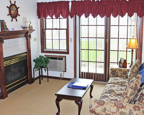A well furnished living room with fireplace and outdoor view.
