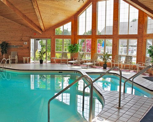 Indoor swimming pool with a hot tub and chaise lounge chairs.