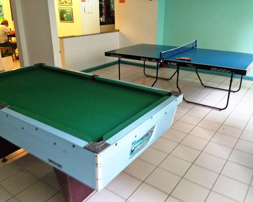 An indoor recreational room with pool table and ping pong table.