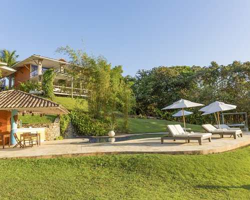 Scenic exterior view of Casa Caiada with chaise lounge chairs and sunshades.