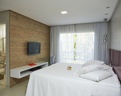 A well furnished bedroom with a television and outdoor view.