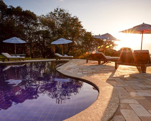 An outdoor swimming pool with chaise lounge chairs and sunshades at dusk.